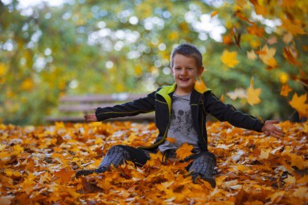Момче с дислексия си играе с падналите листа