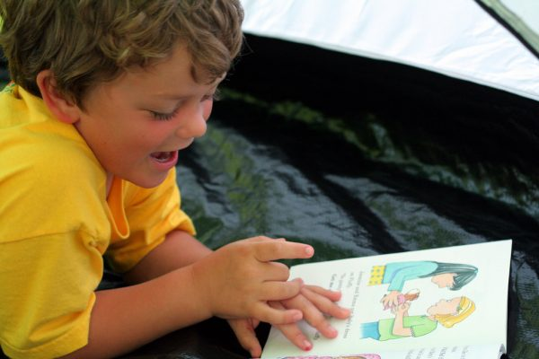 boy-reading-a-book-in-a-tent