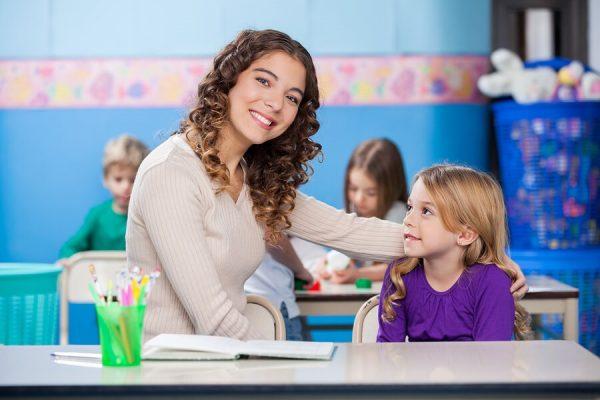 teacher-sitting-next-to-a-schoolgirl